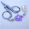 Folding scissors with purple charm.