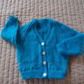 Size 12 -18 months: Unisex cardigan in aqua blue with white pattern above band