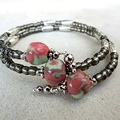 3 handmade porcelain beads in pink, green, grey on memory wire bracelet. Ceramic