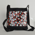 Black bag with red and white flowers double front pocket. Across body handbag