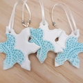 Christmas decorations. Snowflakes with turquoise doily imprint. Ceramic ornament