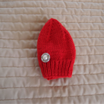 Newborn hand knitted beanie in red with large pearl button; washable