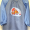 Age 5-8 years. Art smock with light blue sleeves and cement truck