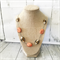 Silver chain necklace with orange and gold patterned lampwork beads.