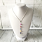 Silver chain chakra reiki necklace with red, pink, yellow and purple beads.