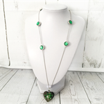 Silver chain necklace with green lampwork heart and flower charm.