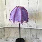 Purple fabric covered lampshade with purple lace overlay and purple beaded trim