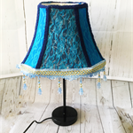 Lampshade with blue lace overlay and blue beaded trim.