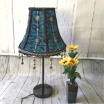 Turquoise fabric covered lampshade with black lace overlay and black beaded trim