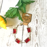 Silver bracelet with red rectangle glass cabochon beads.