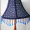 Lampshade with blue flower fabric and blue beaded trim.