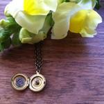 Teensy little golden watch part locket pendant.