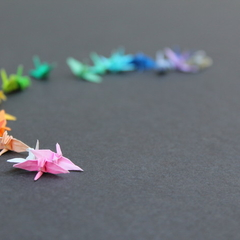 21 mini, micro origami paper cranes in a range of rainbow shades