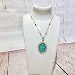 Silver chain necklace with cyan green and black glass oval pendant.