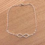 Silver ankle bracelet with infinity rhinestone connector.