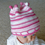 Funky hat: pink and white with pompoms.