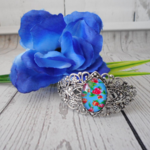 Silver filigree cuff bangle with electric blue and pink rose flower bead.