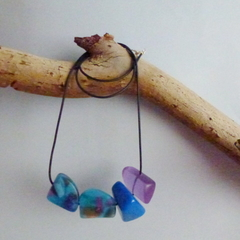Shades of aqua and purple resin bead necklace on black cord