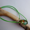 Single green resin bead necklace on green cord