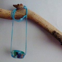 Single blue resin bead, with white, orange and green flecks on blue cord