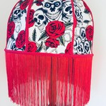 Red and black day of the dead lampshade with red tassel fringe.