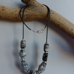 Black, grey and white beaded necklace on black cord
