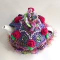 Pretty floral embellished crochet tea cosy in pink and purple. One of a kind.