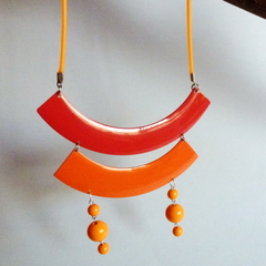Recycled metal disc necklace in shades of orange on orange cord