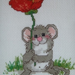 Cross stitched mouse holding a large poppy