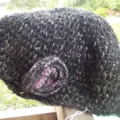 crocheted cloche made from acrylic yarn. Black, pink and yellow with flower