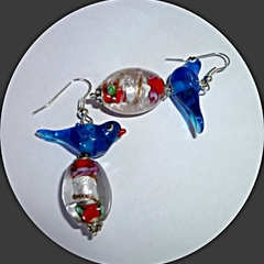 Blue glass bird is sitting on an oval handmade glass bead.