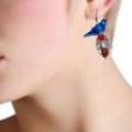 Blue glass bird is sitting on an oval handmade glass bead.