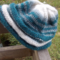 knitted beanie made from pure wool in teal, grey and white.