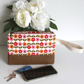 Pink floral clutch bag with wrist strap