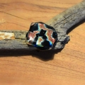 Red, gold, orange, green, blue and black fused glass ring.