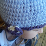 crocheted cloche made from acrylic yarn. lilac, purple and white with flower