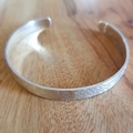 Silver raw silk  textured cuff bangle, large size.