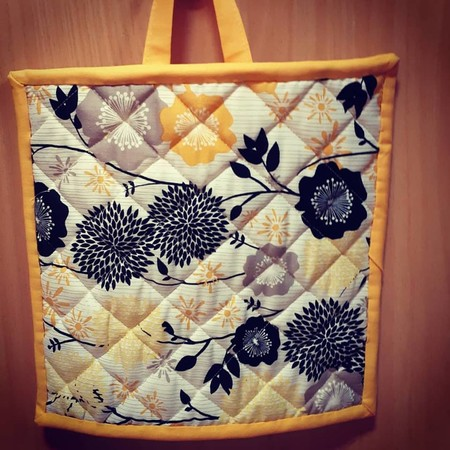 Orange/ Yellow/ Black Floral pot holder with matching spots on reverse