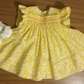 Hand smocked and embroidered dress in yellow with white floral print. Size 00