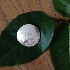 Recycled silver pendant with a dandelion design and peridot