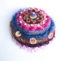A unique  hat for 15 years to adult  featuring many colours and embellishments.