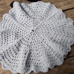 Round crochet washcloth in pale blue bamboo fibre