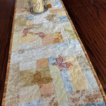 Cream, white and beige scrappy quilted table runner with embroidered butterflies