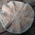 Round crochet washcloth in peach and blue bamboo fibre.