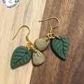 Eucalyptus green polymer clay leaf earrings, with a small glittery gold clay pet