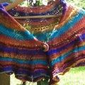 Knitted shoulder or hip wrap made from bright silk blend yarn with button brooch
