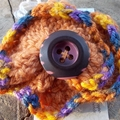 Crocheted hair clip or brooch. Orange and purples with vintage button