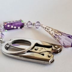 Folding scissors with purple beaded scissor weight.