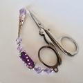 Folding scissors with purple beaded scissor weight.