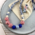 Handcrafted polymer clay adjustable necklace in blue red floral on leather cord